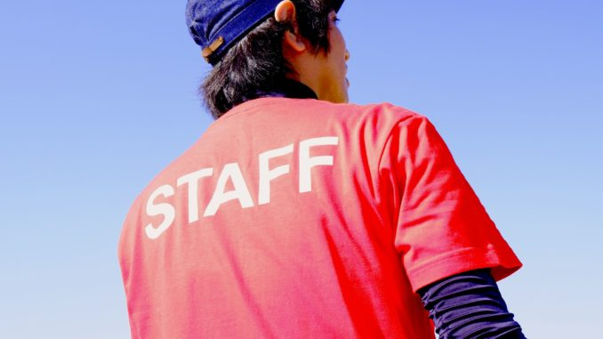 male staff wearing red t-shirt and blue hat standing